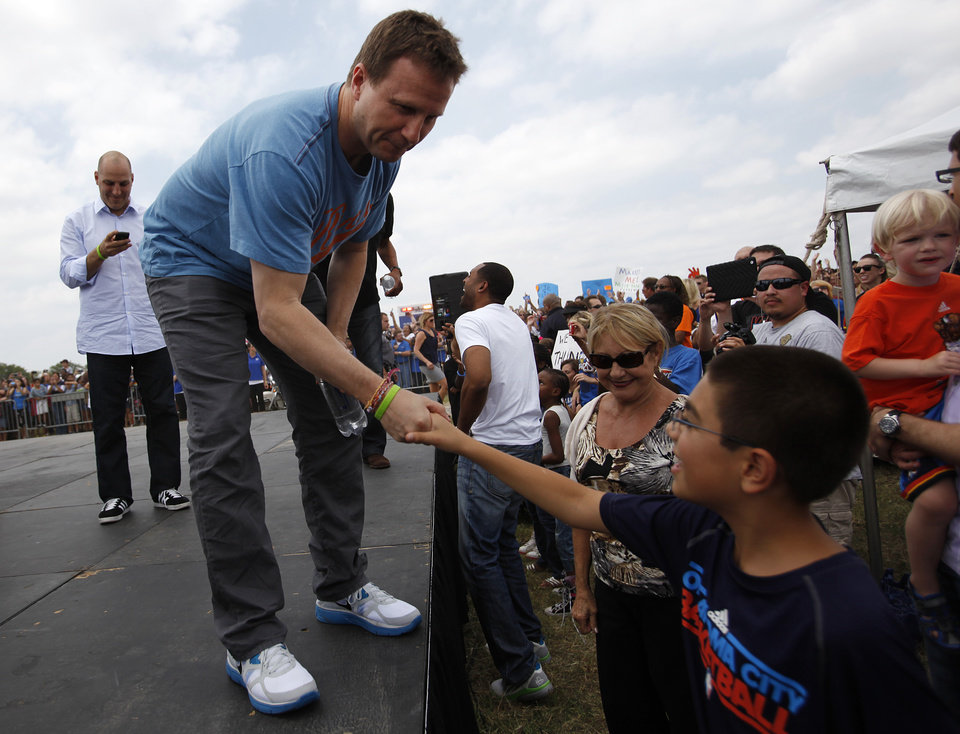 Photo - Oklahoma City Thunder coach, Scott Brooks, greets Mason Kalamian, 10, son of coach Rex Kalamian, during a welcome home rally for the Oklahoma City Thunder at a field near Will Rogers Airport in Oklahoma City, Friday, June 22, 2012.  Photo by Garett Fisbeck, The Oklahoman