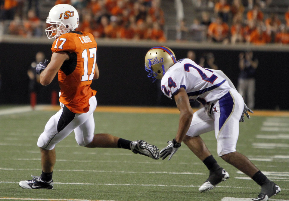 Photo - Oklahoma State's Charlie Moore (17) makes a catch in front of Tulsa's Charles Davis (24) during the college football game between the University of Tulsa (TU) and Oklahoma State University (OSU) at Boone Pickens Stadium in Stillwater, Oklahoma, Saturday, September 18, 2010. Photo by Sarah Phipps, The Oklahoman