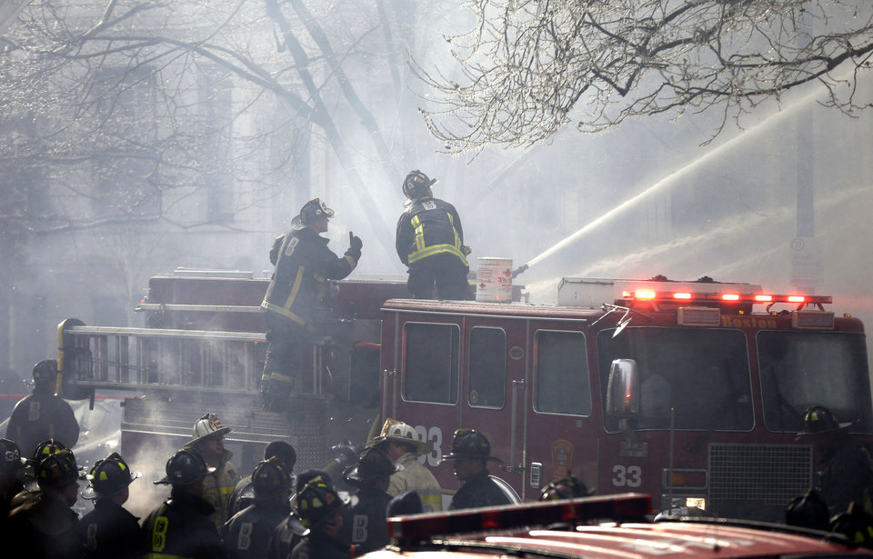Photo - ADDS LAST SENTENCE - Fighters battle a multi-alarm fire at a four-story brownstone in the Back Bay neighborhood near the Charles River, Wednesday, March 26, 2014, in Boston. A Boston city councilor said two firefighters have died in a fire that ripped through a brownstone. (AP Photo/Steven Senne)