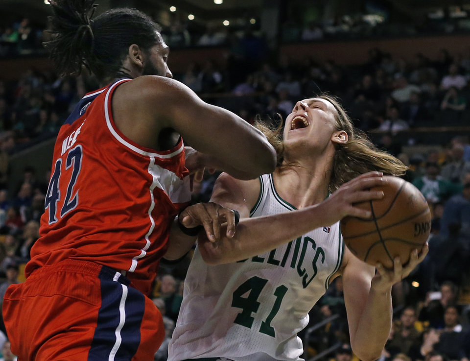 Photo - Boston Celtics center Kelly Olynyk (41) goes up to shoot against Washington Wizards forward Nene Hilario (42) during the second half of an NBA basketball game in Boston, Wednesday, April 16, 2014. The Wizards won 118-102. (AP Photo/Elise Amendola)