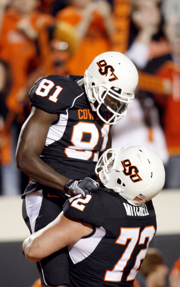 Photo - OSU's Justin Blackmon (81) and Andrew Mitchell (72) celebrate a touchdown during the college football game between Oklahoma State University (OSU) and the University of Colorado (CU) at Boone Pickens Stadium in Stillwater, Okla., Thursday, Nov. 19, 2009. Photo by Sarah Phipps, The Oklahoman