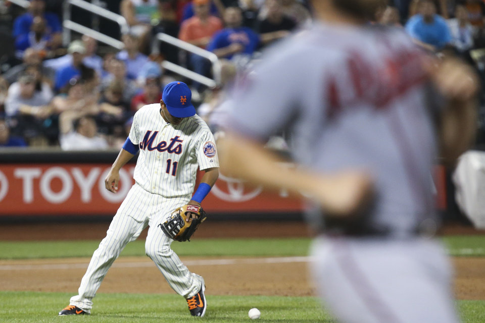 Photo - New York Mets shortstop Ruben Tejada (11) makes a fielding error to let Atlanta Braves' Evan Gattis, right, get safely to first on a single in the third inning of a baseball game, Wednesday, Aug. 27, 2014, in New York. Braves Freddie Freeman scored on the hit. (AP Photo/John Minchillo)