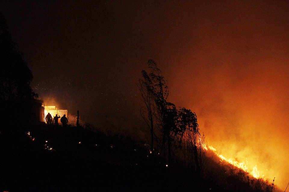 Photo - People prepare to leave as a forest fire rages towards urban areas in the city of Valparaiso, Chile, Sunday April 13, 2014. Authorities say the fires have destroyed hundreds of homes, forced the evacuation of thousands and claimed the lives of at least seven people.  ( AP Photo/ Luis Hidalgo)