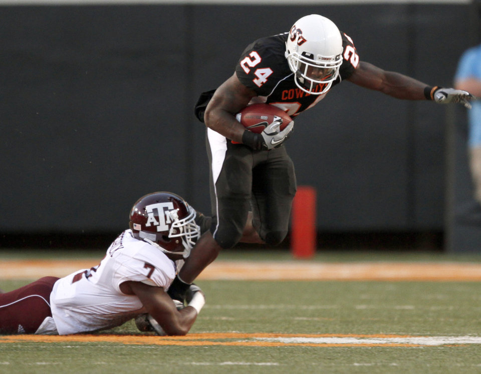 Photo - OSU's Kendall Hunter is brought down by Texas A&M's Terrence Frederick during the college football game between Texas A&M University and Oklahoma State University (OSU) at Boone Pickens Stadium in Stillwater, Okla., Thursday, Sept. 30, 2010. Photo by Bryan Terry, The Oklahoman