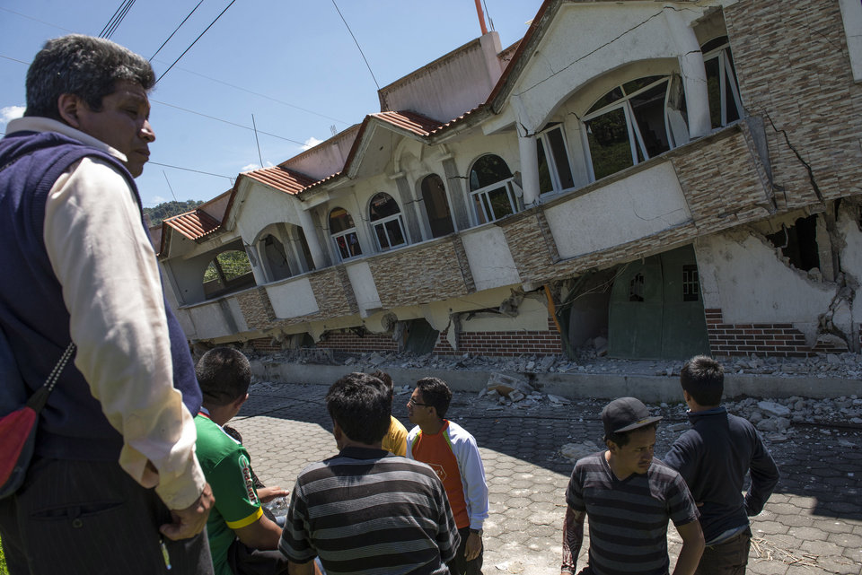 Photo - Neighbors gather outside homes that collapsed during an earthquake in San Pedro, Guatemala, Monday, July 7, 2014. A magnitude-6.9 earthquake on the Pacific Coast jolted a wide area of southern Mexico and Central America Monday. (AP Photo/Oliver de Ros)