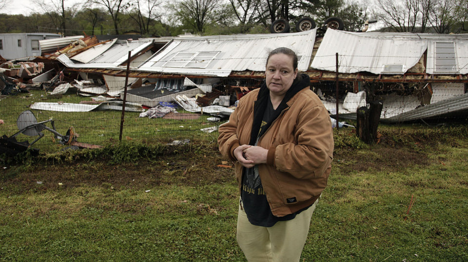 Sherry Gallowich stands in front of her mobile home that was destroyed by a storm , Thursday, April 18, 2013 in Spavinaw, Okla. Middle America was overwhelmed by weather Thursday, with snow in the north, tornadoes in the Plains, and torrential rains that caused floods and transportation woes . Tornadoes caused scattered damage in Oklahoma. Frost warnings were in effect in Kansas and Oklahoma as a cold front pushed out warmer air. (AP Photo/Tulsa World, Mike Simons )  ONLINE OUT; TV OUT; TULSA OUT