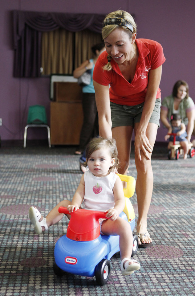 "Keisa Snyder gives a push to her 15-month-old daughter Taylor during ""Playtime for Toddlers"" at the Edmond Library in Edmond, OK, Tuesday, Aug. 31, 2010. By Paul Hellstern, The Oklahoman"