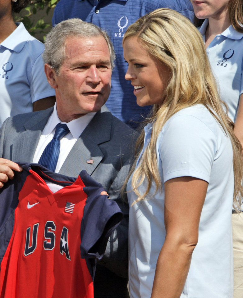 In this July 21, 2008, file photo, President Bush talks with U.S. Olympic Softball pitcher Jennie Finch, talks in the Rose Garden of the White House in Washington, during an event honoring the 2008 United States Summer Olympic Team. Bush is so emphatic about going to the Olympics in China that one might think flying halfway around the globe to attend the games is what presidents do.  (AP Photo/Ron Edmonds)