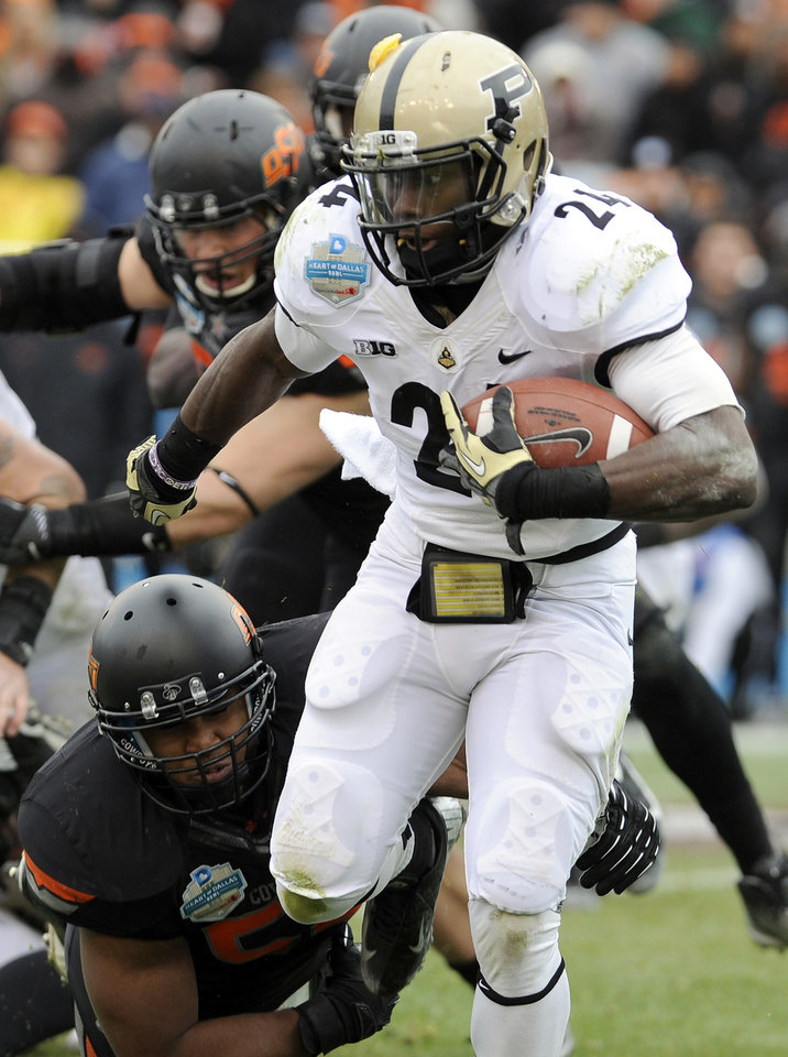 Photo - Purdue running back Akeem Shavers (24) looks for running room around Oklahoma State linebacker Ryan Simmons, bottom, during the first half of the Heart of Dallas Bowl NCAA college football game, Tuesday, Jan. 1, 2013, in Dallas. (AP Photo/Matt Strasen)