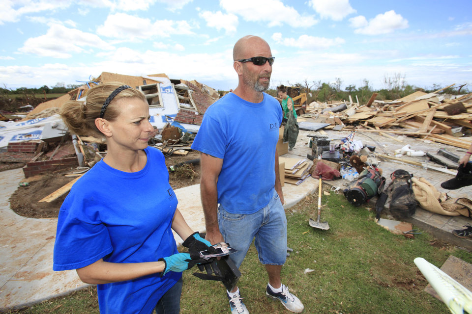 Photo - TORNADO / DAMAGE / AFTERMATH / CLEAN UP / HOUSE: Tornado aftermath cleanup east of Piedmont, Wednesday, May 25, 2011. Duane Johnson and wife Tiffany look over their home that was hit by a tornado Tuesday evening. Photo by David McDaniel, The Oklahoman  ORG XMIT: KOD