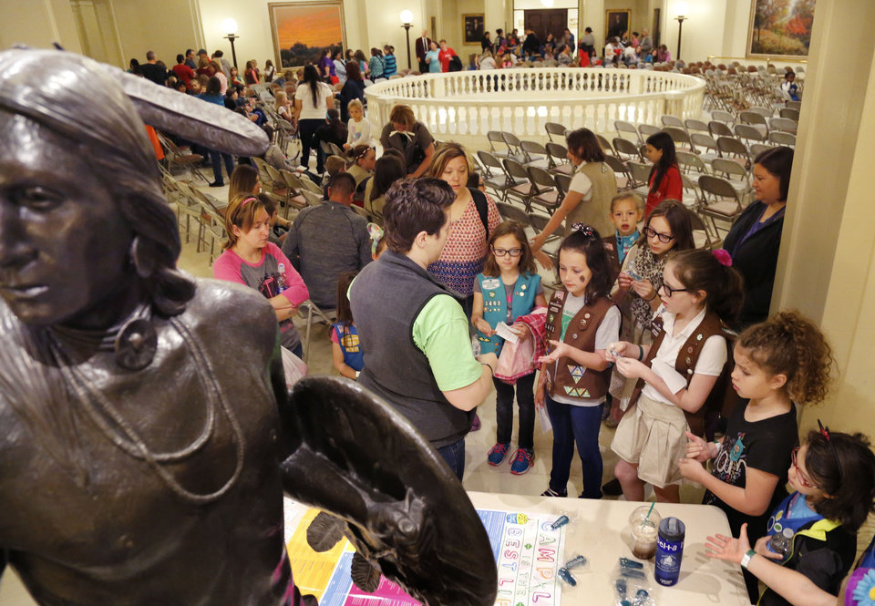 Photo -  Girl Scouts receive key rings and other items Tuesday at one of many booths during