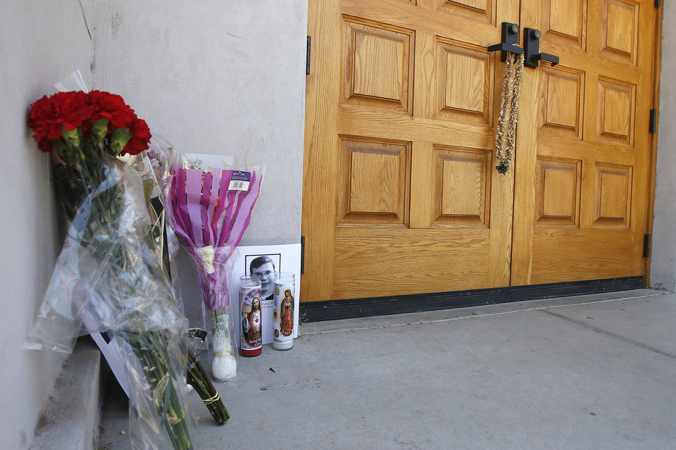 Photo - A makeshift memorial is set up for the Rev. Kenneth Walker, at the Roman Catholic church the Mother of Mercy Mission on Thursday, June 12, 2014, in Phoenix, after a Wednesday evening attack left Walker shot and killed and the Rev. Joseph Terra critically injured.  Police have no suspects at this point, but they are canvassing the neighborhood and going over physical evidence from the scene. (AP Photo/Ross D. Franklin)