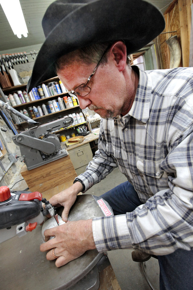 Photo - Ranch foreman James Coldren works on a  belt buckle made from cattle horns on a ranch near Foraker.   David McDaniel - The Oklahoman