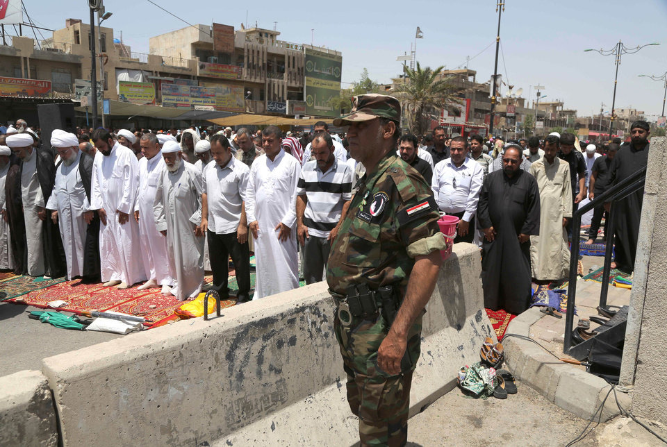 Photo - A member of the Iraqi security forces stands next to followers of Shiite cleric Muqtada al-Sadr attending open-air Friday prayers in the Shiite stronghold of Sadr City, Baghdad, Iraq, Friday, July 18, 2014.  (AP Photo/Karim Kadim)