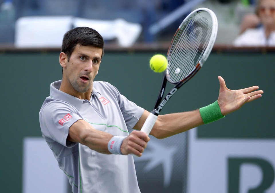 Photo - Novak Djokovic, of Serbia, returns a shot to Alejandro Gonzalez, of Colombia, in a third round match at the BNP Paribas Open tennis tournament, Tuesday, March 11, 2014, in Indian Wells, Calif. (AP Photo/Mark J. Terrill)