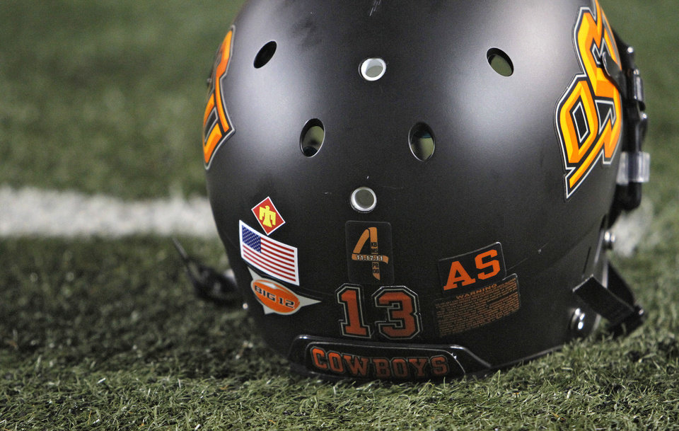 Photo - The OSU helmet during the Bedlam college football game between the Oklahoma State University Cowboys (OSU) and the University of Oklahoma Sooners (OU) at Boone Pickens Stadium in Stillwater, Okla., Saturday, Dec. 3, 2011. Photo by Chris Landsberger, The Oklahoman
