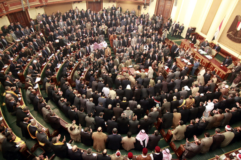 Photo -   FILE - In this Monday, Jan. 23, 2012 file photo, members of parliament stand and pray for the souls of the victims who died during the uprising that ousted President Hosni Mubarak during the first Egyptian parliament session after the revolution, in Cairo, Egypt. Egypt's highest court has ordered the country's Islamist-dominated parliament dissolved, saying its election about six months ago was unconstitutional. The Supreme constitutional Court ruled Thursday that a third of the legislature was elected illegally. As a result, it says in its explanation of the ruling,