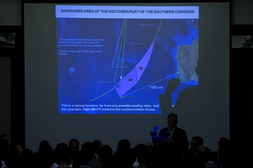 Photo - Lt. Gen. Ackbal Abdul Samad, Malaysian Air Force Air Operation Commander, answers a question from relatives of Chinese passengers on board Malaysia Airlines Flight 370, while the projection shows a graphic of the flight's possible crash area, during a briefing meeting at a hotel in Beijing, China, Wednesday, March 26, 2014. The search of the missing Malaysian airliner resumed Wednesday after fierce winds and high waves forced crews to take a break Tuesday. A total of 12 planes and five ships from the United States, China, Japan, South Korea, Australia and New Zealand were participating in the search, hoping to find even a single piece of the jet that could offer tangible evidence of a crash and provide clues to find the rest of the wreckage. (AP Photo/Alexander F. Yuan)