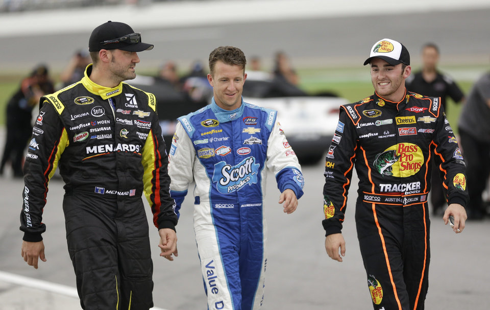 Photo - From left to right, Paul Menard, AJ Allmendinger and Austin Dillon walk back to the garage area after rain stopped qualifying for the Sprint Cup Series auto race at Daytona International Speedway in Daytona Beach, Fla., Friday, July 4, 2014. (AP Photo/John Raoux)