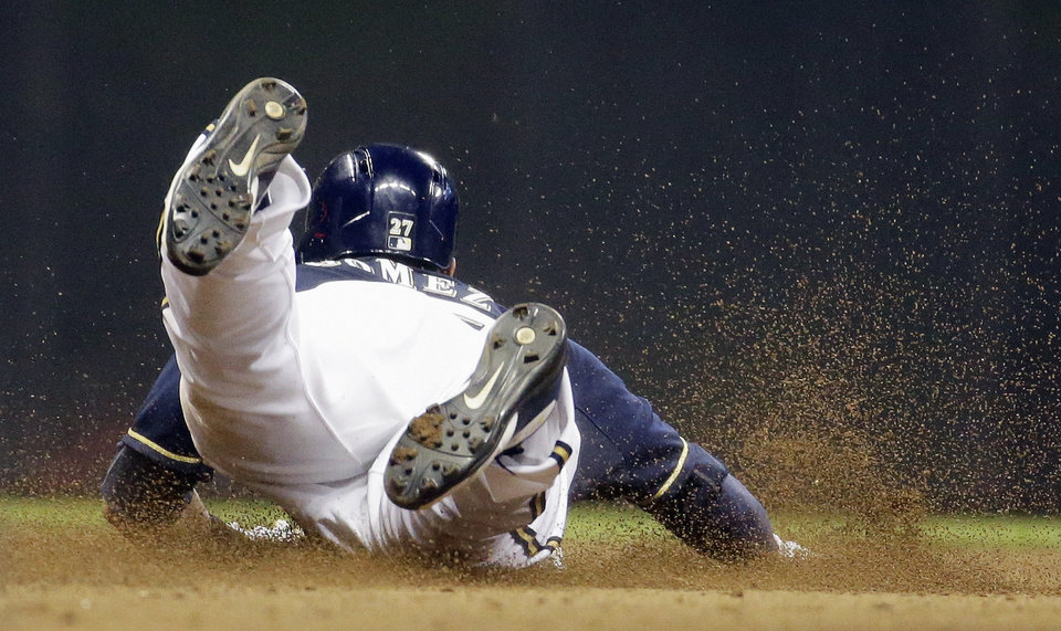 Photo - Milwaukee Brewers' Carlos Gomez steals second during the seventh inning of a baseball game against the Colorado Rockies on Thursday, June 26, 2014, in Milwaukee. (AP Photo/Morry Gash)