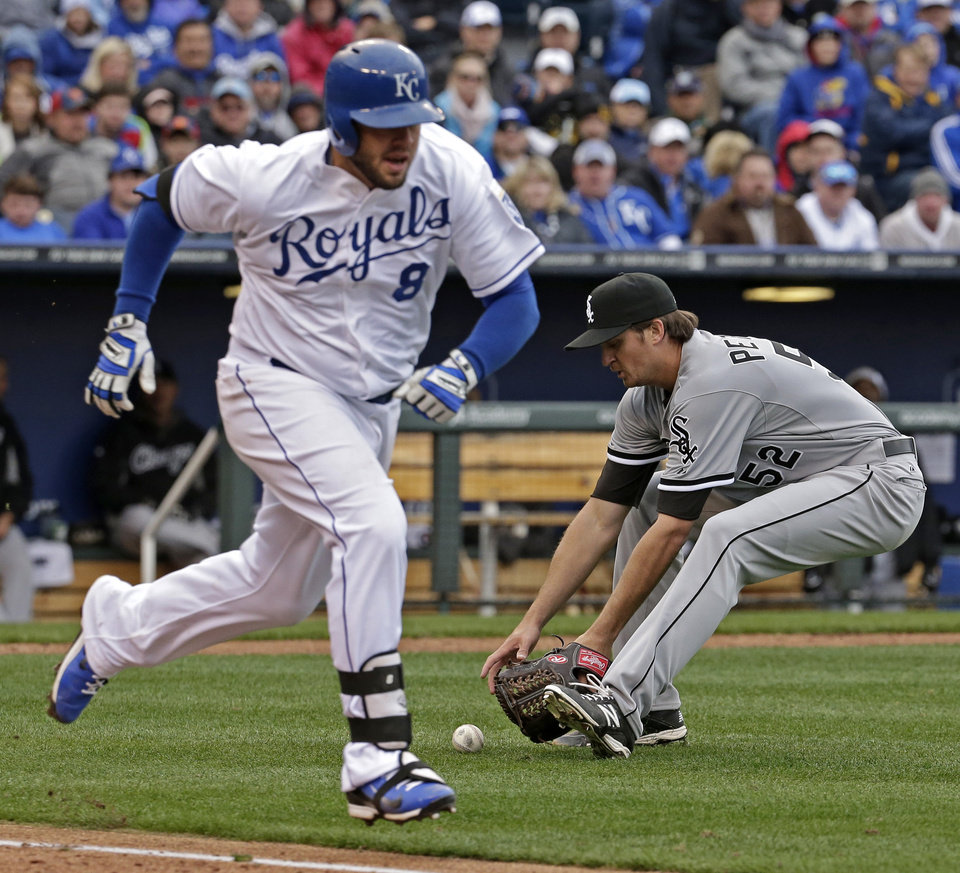 Photo - Chicago White Sox pitcher Jake Petricka (52) fields a ball hit by Kansas City Royals' Mike Moustakas (8) before throwing to first for the out during the sixth inning of a home opener baseball game on Friday, April 4, 2014, in Kansas City, Mo. (AP Photo/Charlie Riedel)