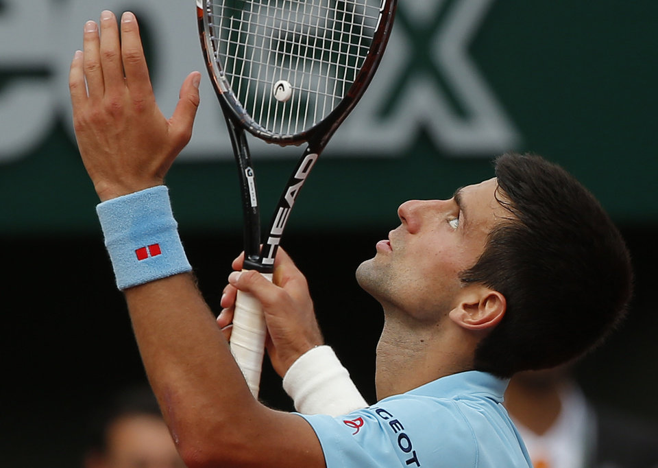 Photo - Serbia's Novak Djokovic reacts as he plays Spain's Rafael Nadal during their final match of  the French Open tennis tournament at the Roland Garros stadium, in Paris, France, Sunday, June 8, 2014. (AP Photo/Michel Euler)