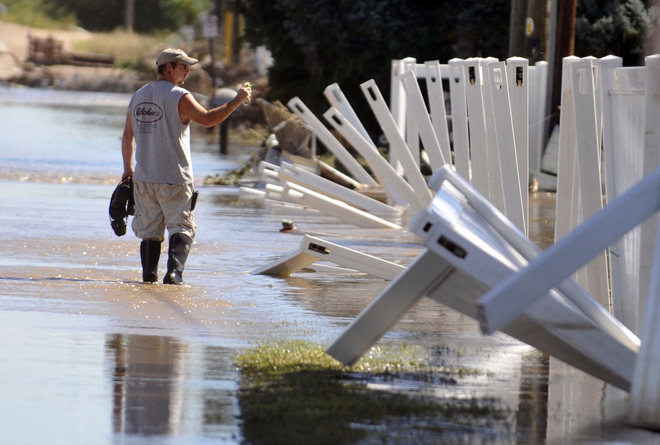 Photo - A man wades through the flood waters Sept. 18, 2013 in Evans, Colo. Residents are advised to wash everything that comes in contact with the water. (AP Photo/The Greeley Tribune, Joshua Polson)