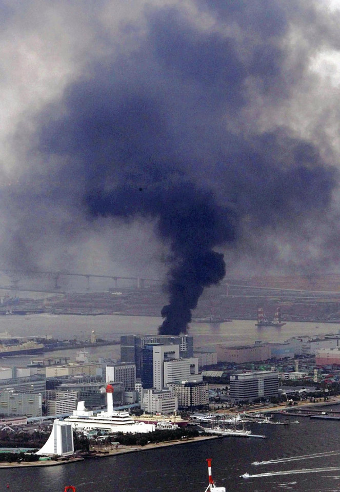 Photo - Black smoke rises from a building in Tokyo's Odaiba bay area after strong earthquakes hit Japan Friday, March 11, 2011. (AP Photo/Yasushi Kanno, The Yomiuri Shimbun)  JAPAN OUT, CREDIT MANDATORY ORG XMIT: TOK828
