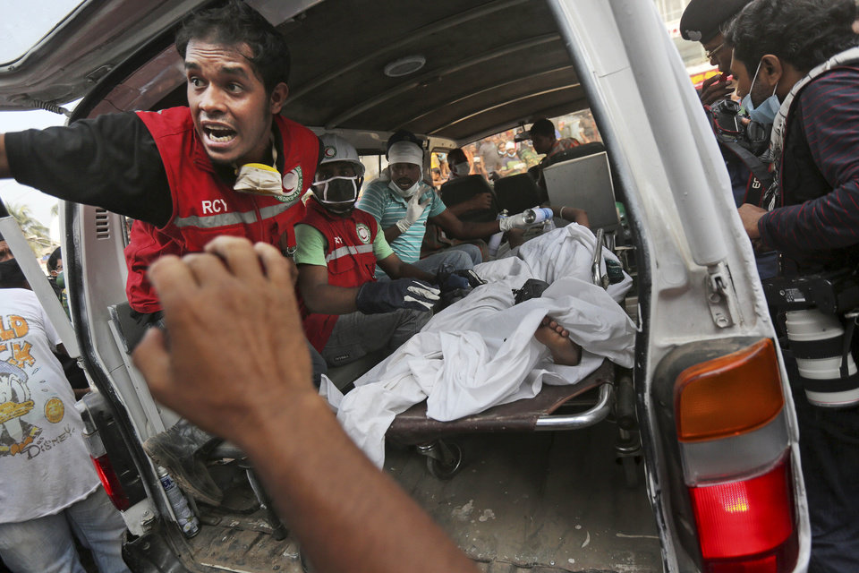 Photo - A Bangladeshi garment worker who was pulled alive from the rubble lays in the back of an ambulance after being brought by rescue workers at the site of a building that collapsed Wednesday in Savar, near Dhaka, Bangladesh, Friday, April 26, 2013. The death toll reached hundreds of people as rescuers continued to search for injured and missing, after a huge section of an eight-story building that housed several garment factories splintered into a pile of concrete.(AP Photo/Kevin Frayer)