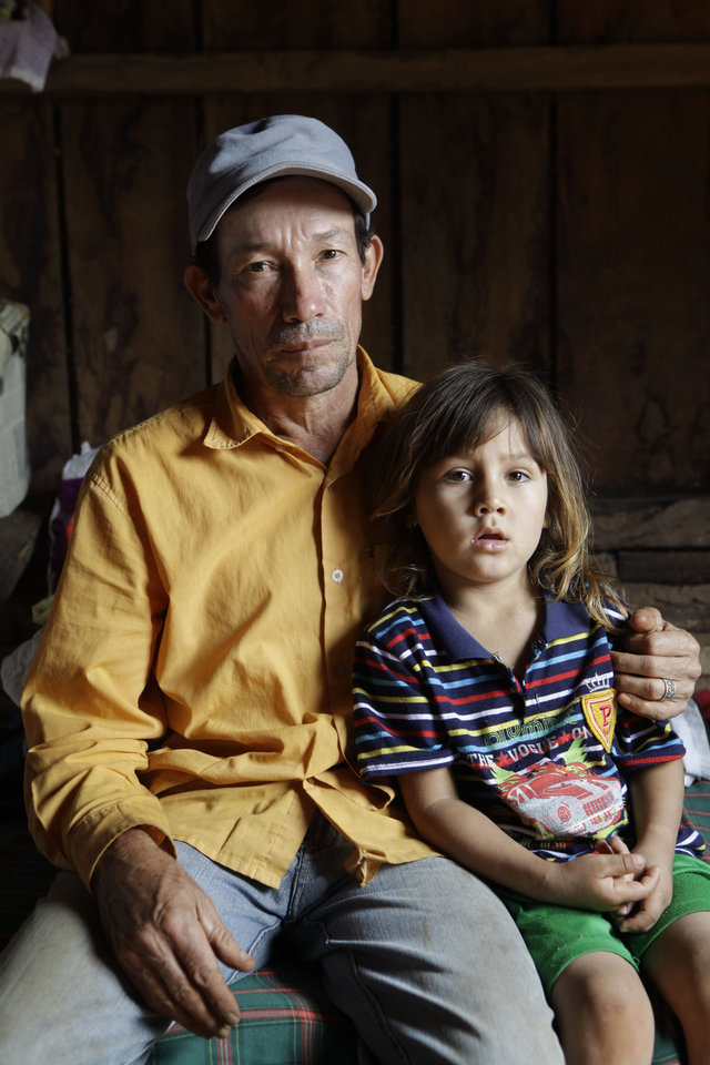 In this Nov. 7, 2012 photo, Mariano Castro, left, poses for a portrait with his grandson Mario Castro Rodriguez in the Yvy Pyta settlement near Curuguaty, Paraguay. Castro's son Adolfo was killed and his two other sons Adalberto and Nestor were imprisoned during the �Massacre of Curuguaty� on June 15 when negotiations between farmers occupying a rich politician's land ended with a barrage of bullets that killed 11 farmers and 6 police officers. (AP Photo/Jorge Saenz)