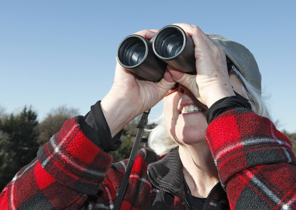 Photo - Susy Hall uses her binoculars to watch birds Tuesday at Mitch Park in Edmond. Photo By David McDaniel, The Oklahoman  David McDaniel