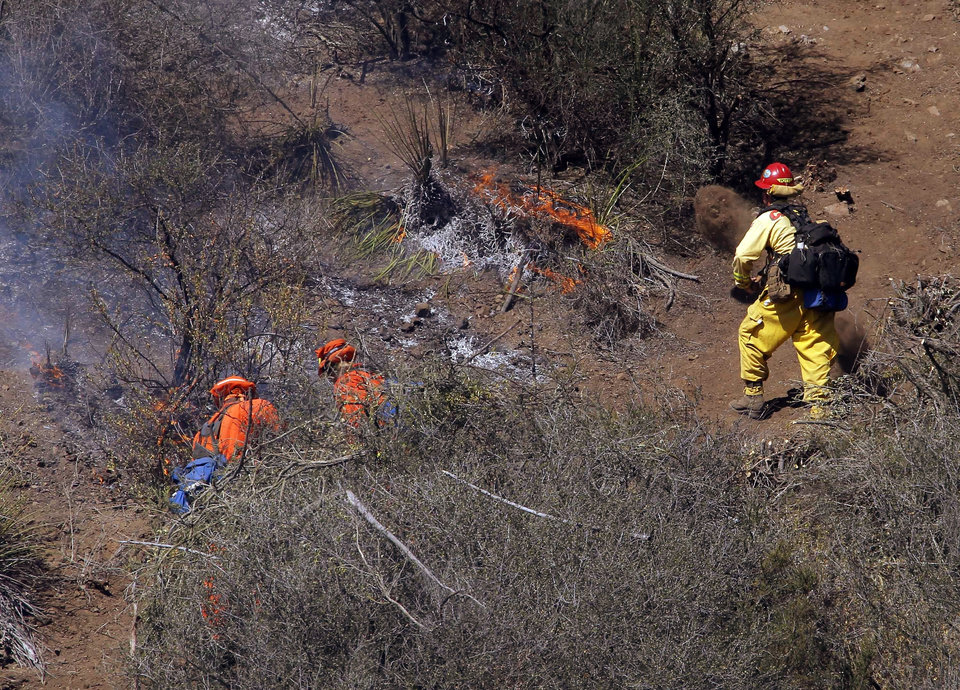 Photo - Firefighters clean up a hotspot burning over a hill near Thousand Oaks, Calif., on Thursday, May 2, 2013. The blaze erupted during morning rush hour along U.S. 101 in the Camarillo area about 50 miles west of Los Angeles. It quickly charred more than 10 square miles because of winds that have also pushed other damaging blazes across the region. (AP Photo/Nick Ut)