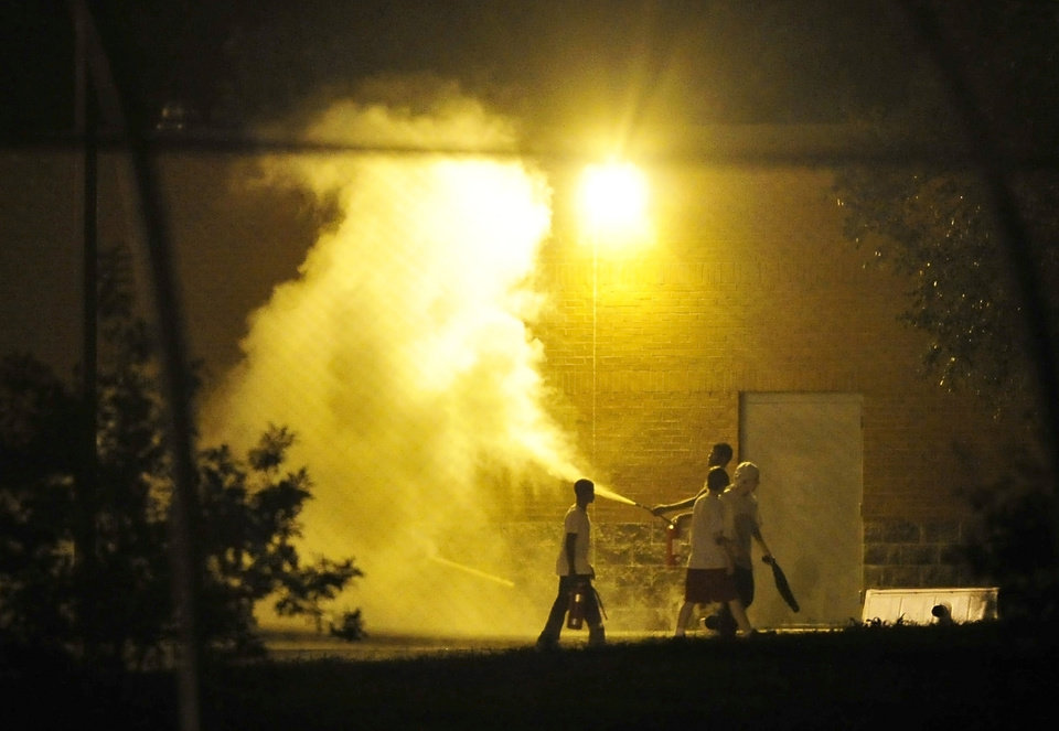 Photo - Teenagers spray a fire extinguisher at the Woodland Hills Youth Development Center in Nashville, Tenn., early Thursday, Sept. 4, 2014. More than two dozen teens created a large disturbance Wednesday night in the yard of a detention center with a long history of violence, escape attempts and sexual-abuse allegations. Two days earlier, 32 teens escaped from the facility. (AP Photo/The Tennessean, Jason S. Lee)