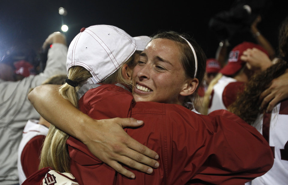 Photo - Kayla Braud (1) hugs graduate assistant Whitney Larsen after beating OU in the Women's College World Series softball championship at ASA Hall of Fame Stadium in Oklahoma City, Thursday, June 7, 2012.  Photo by Garett Fisbeck, The Oklahoman
