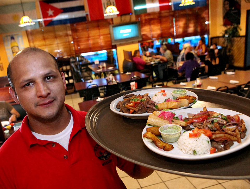 Jorge Zarate poses with a tray of Peruvian food at Zarate's Latin Mexican Grill in Edmond on  Tuesday, July 27, 2009. By John Clanton, The Oklahoman