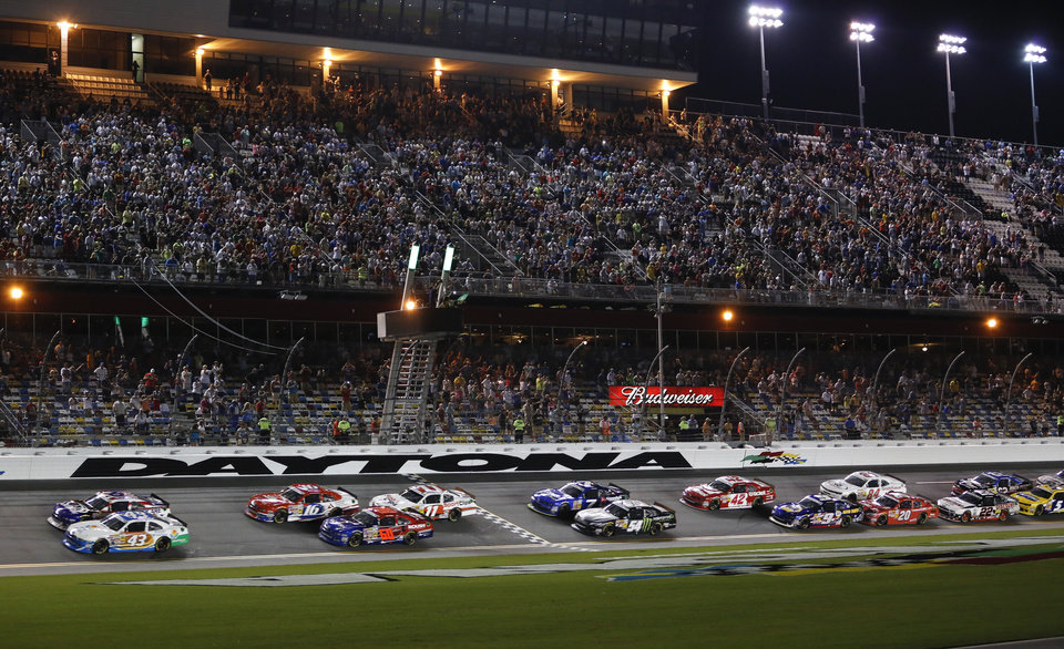 Photo - Trevor Bayne, top left, and Dakoda Armstrong (43) lead the field to start the  NASCAR Nationwide series auto race at Daytona International Speedway in Daytona Beach, Fla., Friday, July 4, 2014. (AP Photo/Terry Renna)