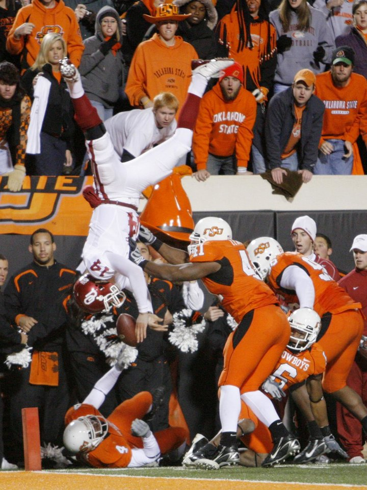 OU quarterback Sam Bradford leaps over Orie Lemon during the second half of the college football game between the University of Oklahoma Sooners (OU) and Oklahoma State University Cowboys (OSU) at Boone Pickens Stadium on Saturday, Nov. 29, 2008, in Stillwater, Okla. STAFF PHOTO BY CHRIS LANDSBERGER