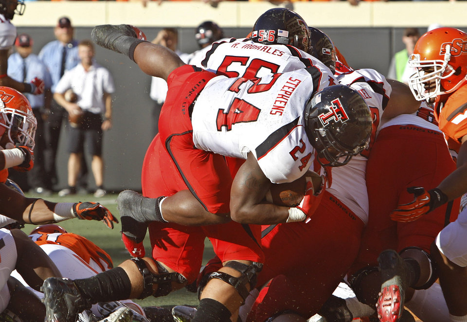 Texas Tech running back Eric Stephens Jr. (24) jumps over the line for a touchdown against Oklahoma State in the second quarter of an NCAA college football game in Stillwater, Okla., Saturday, Nov. 17, 2012. (AP Photo/Sue Ogrocki)