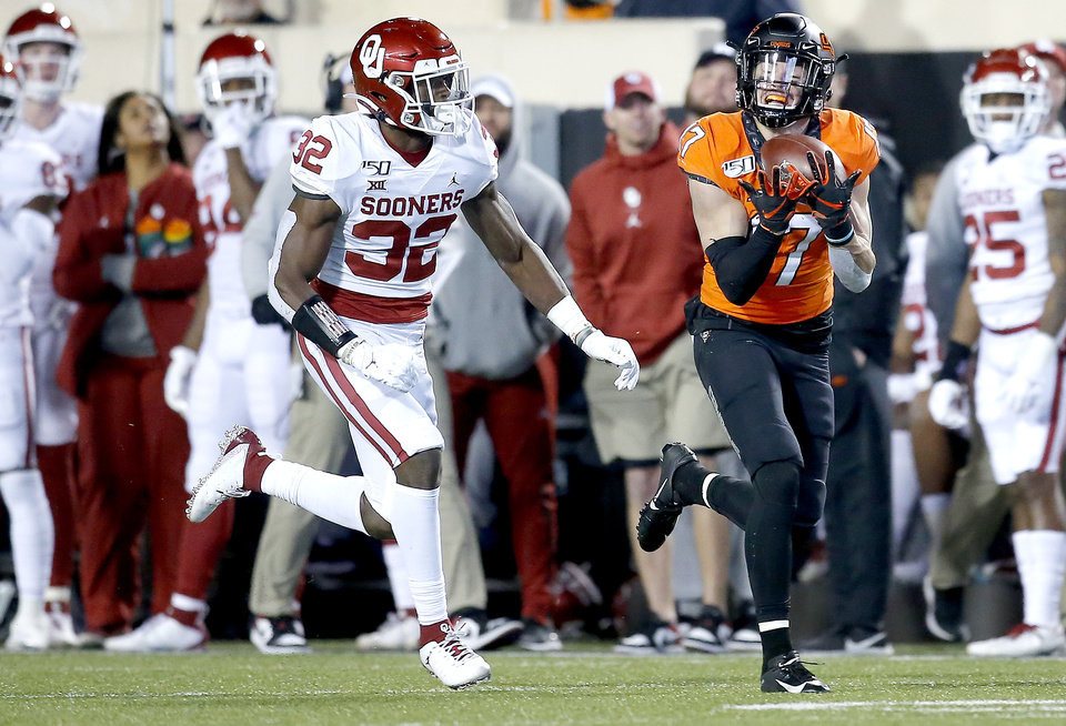 Photo - Oklahoma State's Dillon Stoner (17) makes a catch in front of Oklahoma's Delarrin Turner-Yell (32) in the first quarter during the Bedlam college football game between the Oklahoma State Cowboys (OSU) and Oklahoma Sooners (OU) at Boone Pickens Stadium in Stillwater, Okla., Saturday, Nov. 30, 2019. OU won  34-16. [Sarah Phipps/The Oklahoman]