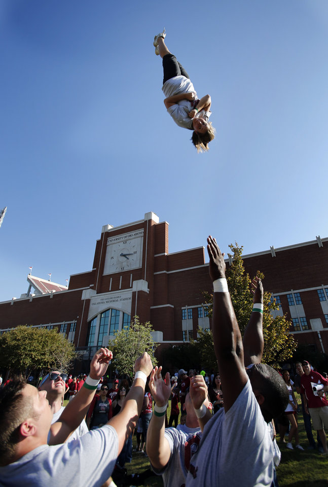 Photo - Cheerleader alumnus Nicole Grazier, Dallas, stunts before the college football game between the University of Oklahoma Sooners (OU) and the University of Kansas Jayhawks (KU) at Gaylord Family-Oklahoma Memorial Stadium in Norman, Okla., on Saturday, Oct. 20, 2012. Photo by Steve Sisney, The Oklahoman