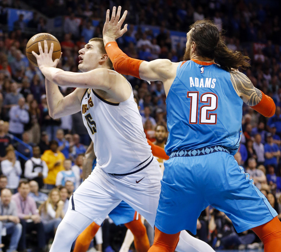 Photo - Denver's Nikola Jokic (15) goes to the basket to score past Oklahoma City's Steven Adams (12) in the fourth quarter during an NBA basketball game between the Denver Nuggets and the Oklahoma City Thunder at Chesapeake Energy Arena in Oklahoma City, Friday, March 29, 2019. Denver won 115-105. Photo by Nate Billings, The Oklahoman