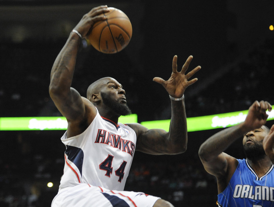Atlanta Hawks forward Ivan Johnson (44) shoots as Orlando Magic forward Kyle O'Quinn defends during the first half of an NBA basketball game on Saturday, March 30, 2013, in Atlanta. (AP Photo/John Amis)