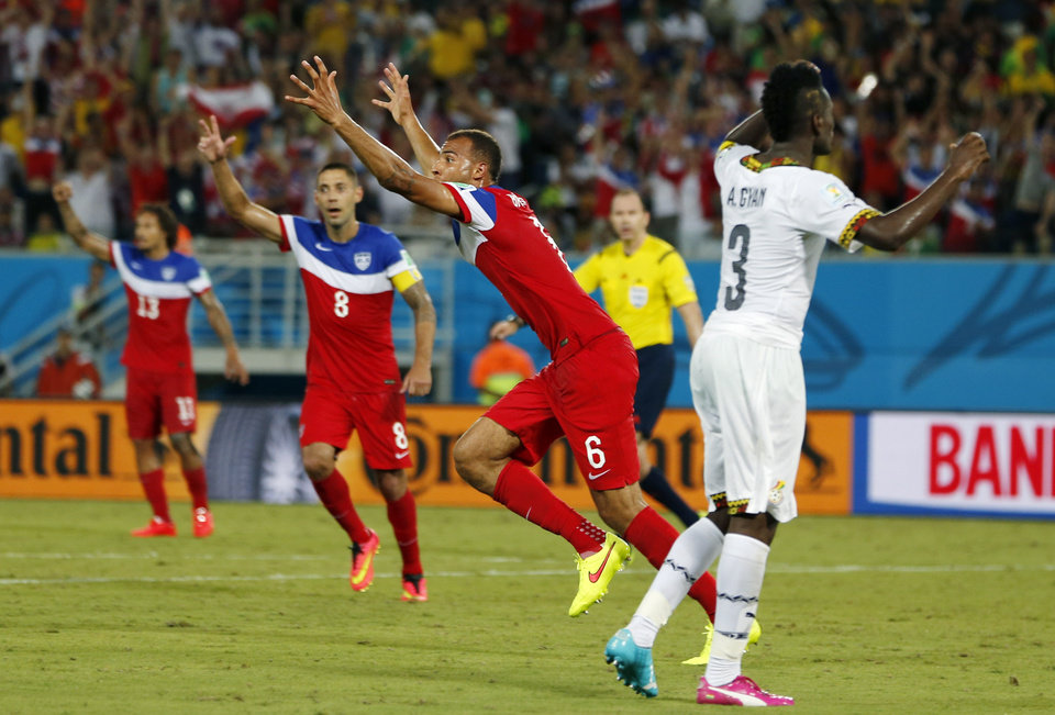 Photo - United States' John Brooks (6) celebrates with teammates after scoring his side's second goal during the group G World Cup soccer match between Ghana and the United States at the Arena das Dunas in Natal, Brazil, Monday, June 16, 2014. (AP Photo/Julio Cortez)
