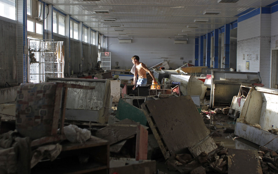 Photo -   A man removes rubbish from a shop in Krimsk, about 1,200 kilometers (750 miles) south of Moscow, Sunday, July 8, 2012. Intense flooding in the Black Sea region of southern Russia killed at least 150 people after torrential rains dropped nearly a foot of water, forcing many to scramble out of their beds for refuge in trees and on roofs, officials said Saturday. (AP Photo/Sergey Ponomarev)