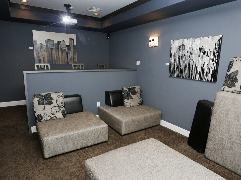 Photo - The home theater room at 17320 White Hawk Drive has plenty of comfy seating.  NATE BILLINGS - The Oklahoman