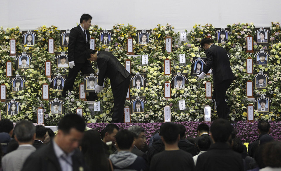 Photo - Funeral service workers set up portraits of victims of the sunken ferry Sewol at a group memorial altar in Ansan, South Korea, Friday, May 9, 2014. South Korean prosecutors are seeking to formally arrest the head of the company that owns a doomed ferry in part of their investigation into its sinking last month that left more than 300 people, mostly high school students, dead or missing, officials said Friday. (AP Photo/Ahn Young-joon)