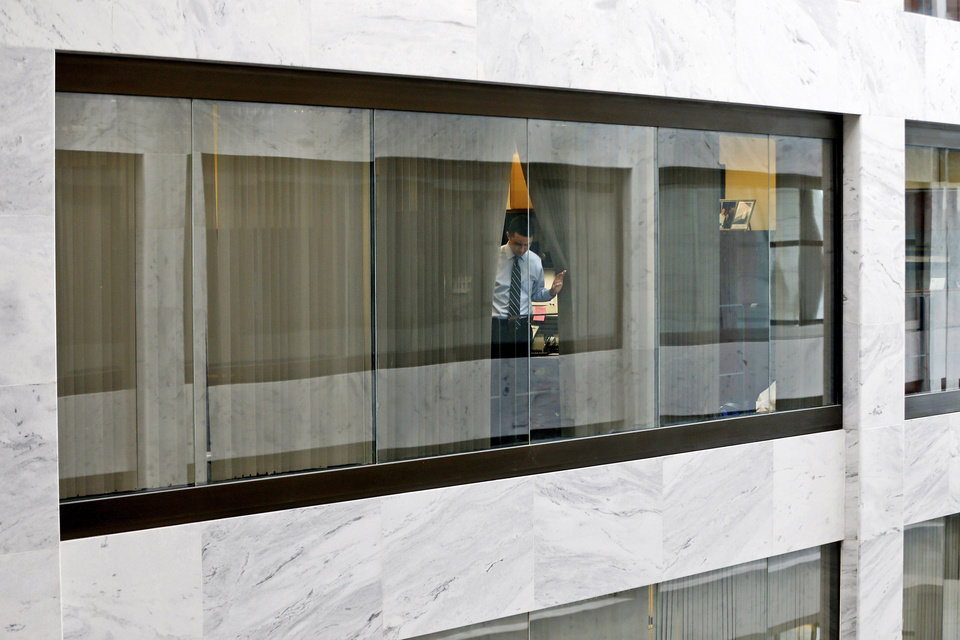 Photo - An unidentified staff member looks out from his office window down into the atrium of the Hart Senate Office Building on Capitol Hill in Washington, Wednesday, April 17, 2013, after they were told to shelter in place after reports of suspicious packages discovered on Capitol Hill. U.S. Capitol police are investigating the discovery of at least two suspicious envelopes in Senate office buildings across the street from the Capitol. (AP Photo/Charles Dharapak)
