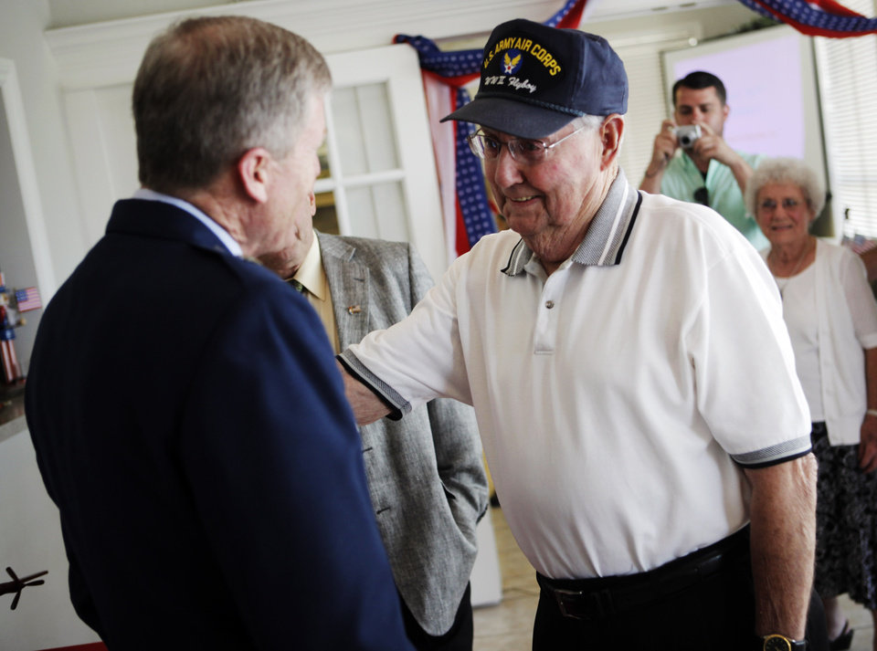 John Martin (right), a World War II veteran of the Army Air Force, meets Greg Ferguson (left), Brigadier General of the Oklahoma Air National Guard, at Martin's 90th birthday party on July 7, 2013. John Martin received three metals, the WWII Victory Medal, American Campaign Medal, and the Army Good Conduct Medal, that he had been awarded in World War II but had not received until 2013. Photo by KT KING, The Oklahoman