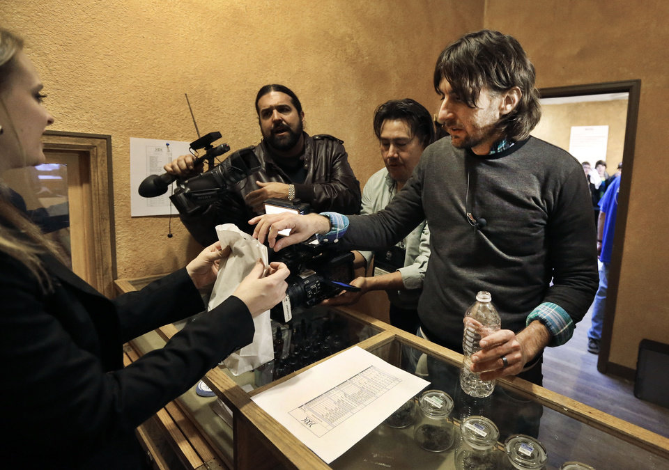"Customer Adam Hartle makes a cash transaction, one of the first to buy retail marijuana at 3D Cannabis Center, which opened as a legal recreational retail outlet in Denver, on Wednesday, Jan. 1, 2014. Colorado began retail marijuana sales on Jan. 1, a day some are calling ""Green Wednesday."" (AP Photo/Brennan Linsley)"