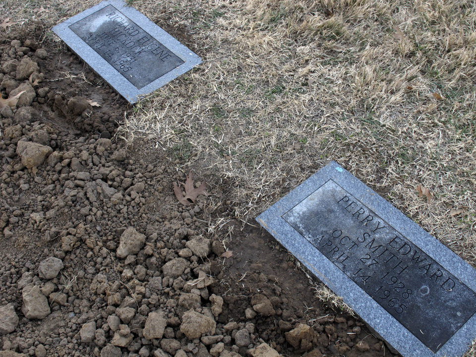 Photo - The graves of convicted and executed murderers Richard Hickock, left, and Perry Smith, right, sit side by side in Mount Muncie Cemetery after the exhumation and reburial of their remains, Tuesday, Dec. 18, 2012, in Lansing, Kan. Their killings of a family in 1959 inspired Truman Capoteís book, ìIn Cold Blood,î and Florida authorities believe they may be tied to decades-old killings there. (AP Photo/John Hanna)